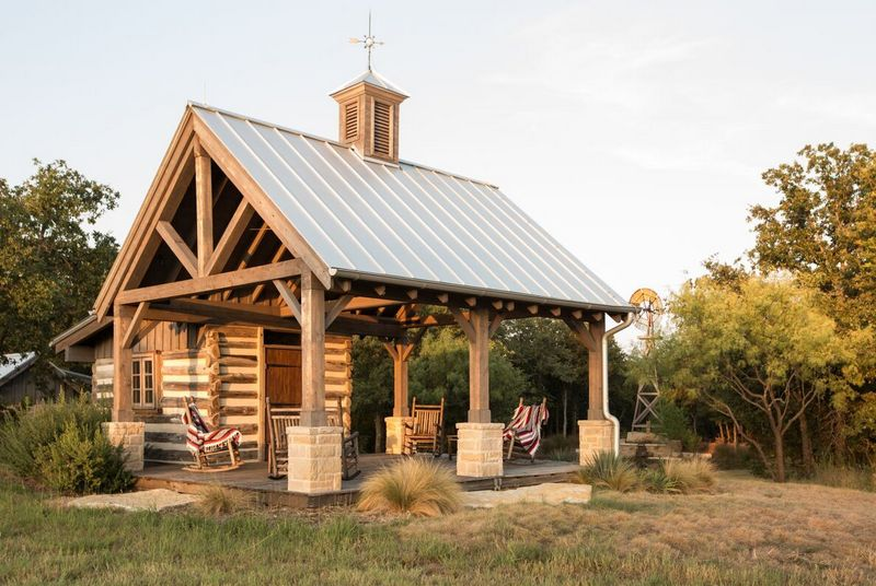 Trail Ride Shelter Made from Antique Log Cabin, with Standing Seam Metal Roof and Antique Weathervane. Design by Dallas Architect, Steve Chambers, A.I.A., Specializing in Custom Ranches and Homes in Texas and Oklahoma.